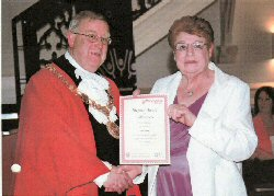 Pam Stevens receiving her award from the Mayor. Click for larger image